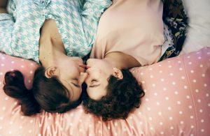 to kvinder der kysser i en seng